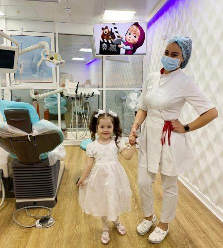 Доктор и маленькая пациентка в детской стоматологии